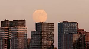 moon behind buildings
